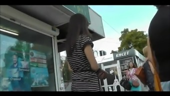 Delightful girl in striped dress taking the bus