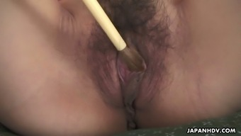 Lewd dude tickles sweet Japanese hottie Yuria Tominaga's pussy with a brush