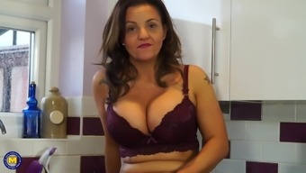 Mature modern mother bating on her kitchen