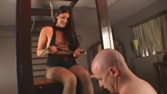 Elegant brunette in high heels and fishnets foot dominates male slave