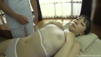 Busty Japanese bomshell Sonoda Mion oiled up and massaged clothed