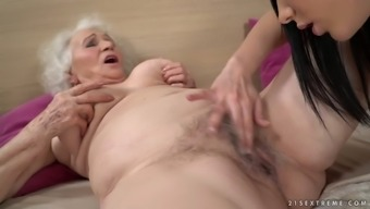 Perverted wrinkled mature whore Norma lets charming brunette work on her twat