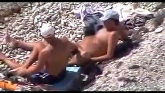 Two mature gay men have fun on a nudist beach